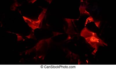 Pieces of hot coals burn with a small flame a flame in the dark