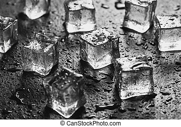 Pieces of ice cubes with water droops on black background.