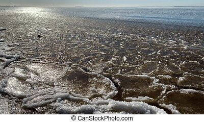 Pieces of ice float on waves, Ice plaques, sandy coast, stones, spring landscape, sunny weather