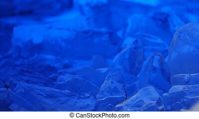 Pieces of ice lies on the table, blue illumination...