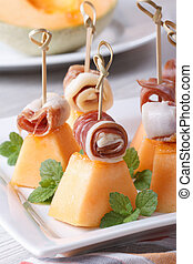 pieces of melon with ham on skewers close up. Vertical -...