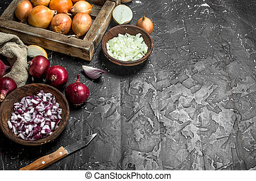 Pieces of onions in a bowl with a yellow onion on tray and red onion in a sack.
