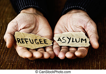 pieces of paper with words refugee and asylum - closeup of ...