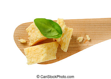Pieces of Parmesan cheese on wooden spatula
