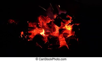 Pieces of red-hot coals burn with a red-blue flame