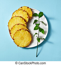 pieces of ripe pineapple and a green twig in a plate on a blue paper background,