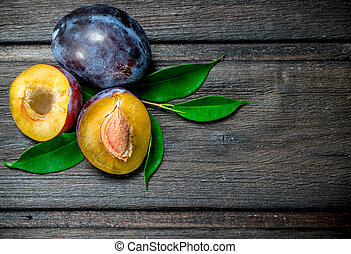 Pieces of ripe plum with leaves.