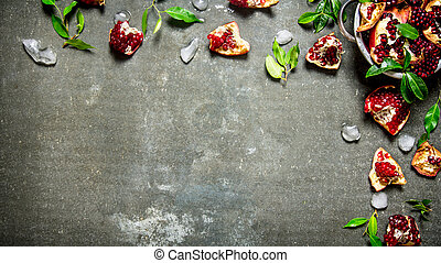 Pieces of ripe pomegranate with leaves and ice in a bowl. On...
