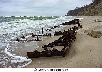 pieces of rusty iron on the seashore, the remains of a ship on the sand