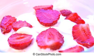 Pieces of strawberries in cream, rotating. Macro shot. seamless looping.