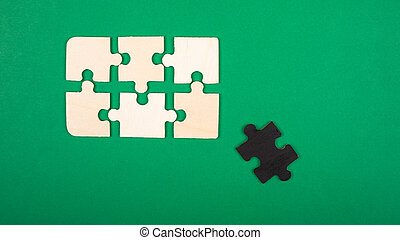 Pieces of the puzzle colors white and black, lie on a green background. outcast antisocial white crow close-up top view