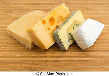 Pieces of various cheese on the bamboo cutting board