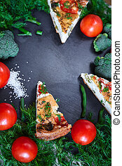 pieces of vegetable pie with cottage cheese, tomatoes, dill and asparagus beans on a dark ceramic background.