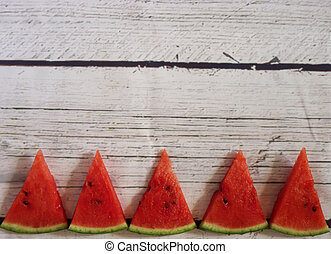 Pieces of watermelon on a white wooden background