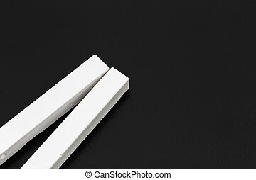 pieces of white chalk photographed over a blackboard