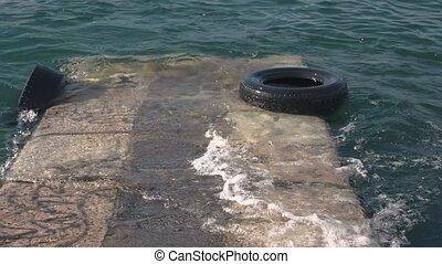Pier and tires. Waves on the lake.