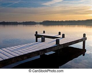 Pier at lake during wintertime sunrise