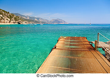 Pier at cove with clear turquoise water in Sardinia
