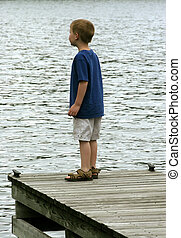 A boy standing on the edge of a pier looking into the distance.