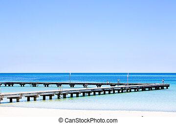 Pier in blue water of the ocean shore