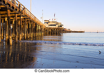 Pier in Santa Barbara - A low, setting sun casts a deep...