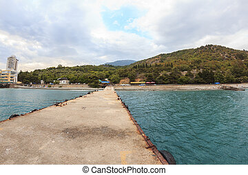 Pier in sea with mountains