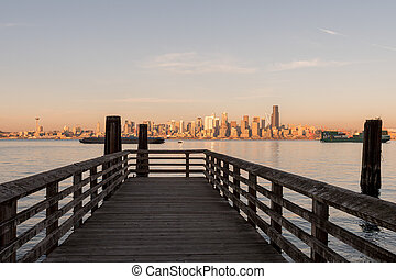 Pier in Seattle Bay with sunset light over downtown skyscrapers in the background, Washington, USA.