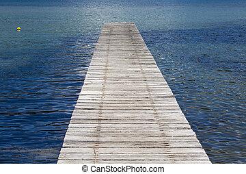 pier into the calm blue sea