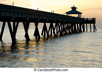 Pier on a beach at sunrise.