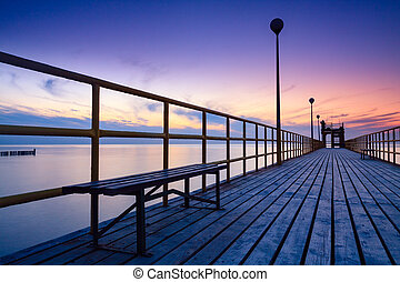Pier on the sea at sunset. Lanterns and benches. Lonely landscape and dramatic sky.