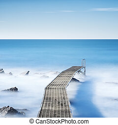 Pier or jetty on a blue ocean in the morning. Long Exposure