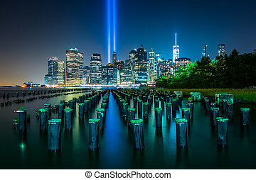 Pier pilings and the Tribute in Light over the Manhattan ...
