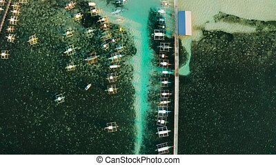 Top view: Boats awaiting tourists and the pier in the city of General Luna on the island of Siargao.