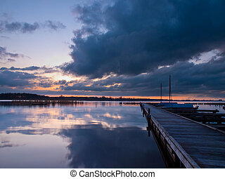 Boats along a jetty during a tranquil sunset