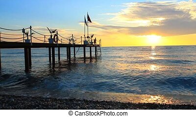 Pier with flag at sunrise in Kemer, Turkey.