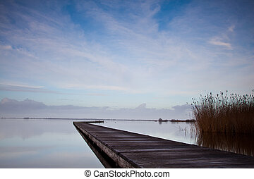 Old Jetty on a Cold Day at a Dutch Lake with Reed and Blue Sky