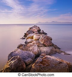 Pier/jetty of rock and stone, playa de muro, alcudia, mallorca, spain, sunrise over mountains, beautiful smooth sea.