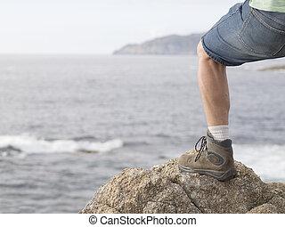 pierna, con, un, bota, en, un, vista marina