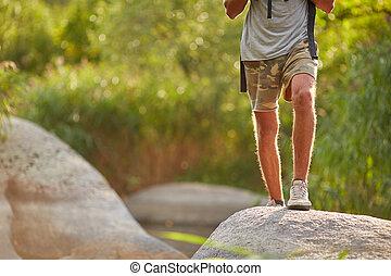 piernas masculinas, excursionismo, en, montaña, peak., viajando arduamente, shoes, en, excursionista, pies, aire libre, cruce, roca, piedras, en, río, creek.