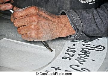 pierre tombale, graveur, au travail