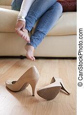 pies, mujer, de, ella, frotamiento, después, joven, zapatos de taco alto, hogar, toma, sentado
