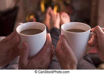 pies, warming, en, chimenea, con, manos, sostener el café