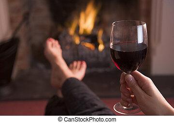 pies, warming, en, chimenea, con, tenencia de la mano, vino