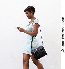 pieszy, kobieta, ruchomy, tekst, telefon, uśmiechanie się, czytanie
