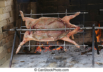 pig cooks slowly on enormous steel spit in the gigantic fireplac
