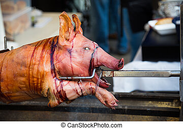 Closeup to a pig on a spit at a festival