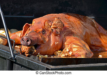 Pig roasting in grill with onions.