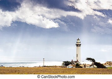 Pigeon Point Lighthouse on the Pacific Ocean coastline; sun rays bursting through storm clouds; Pescadero, San Francisco bay area, California
