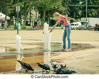 Pigeons drinking water from a public fountain near the entertain the girls.