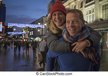 Piggy Back Through Festive City - Mature man is giving his...